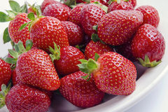 Strawberries. Fresh juicy strawberries on a white plate, close up Royalty Free Stock Images
