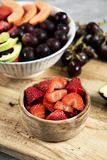 Strawberries and fruit salad in some bowls. Closeup of a boxwood bowl with some strawberries and a ceramic bowl with a fruit salad, made with avocado, papaya royalty free stock photos