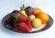 Fruit and berries on a plate. Strawberries and fruits on a plate, white background Stock Photo