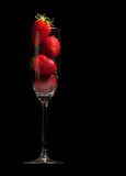 Strawberries in a glass on black background Stock Images