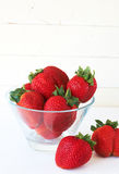 Strawberries in glass bowl. Fresh strawberries in glass bowl against antique white background Royalty Free Stock Photo