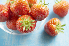 Strawberries in a glass bowl on a blue table Stock Photo