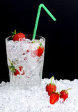 Strawberries in glass of ice. With straw, black background and copy space royalty free stock photos