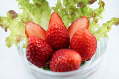 Strawberries in glass. Strawberries put in glass dish with vegetables and strawberries cut into pieces Stock Image