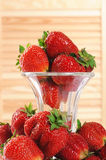 Strawberries in a glass vase on light wood background Stock Photo