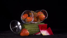 Strawberries in glasses. Closeup of ripe strawberries in two Champagne flute glasses lying on side, black background Stock Images