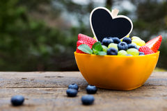 Strawberries, grapes and blueberries on wooden table, black hear Stock Photo