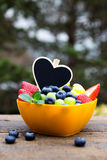 Strawberries, grapes and blueberries on wooden table, black hear Stock Photos