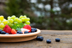 Strawberries, grapes and blueberries on wooden table, outside Royalty Free Stock Photos