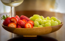 Strawberries Grapes and Wine. Strawberries and grapes in a wooden bowl with a glass of white wine on a wooden table Stock Image