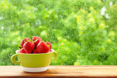 Strawberries in a green cup against the window. A window in the rain drops. Royalty Free Stock Photos