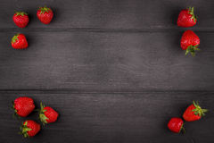 Strawberries with green leaf on dark wooden Royalty Free Stock Image