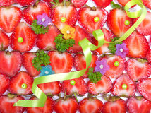 Strawberries, green ribbon and beads background Stock Images