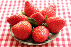 Strawberries. A group of large strawberries in a dish with red gingham background Stock Image