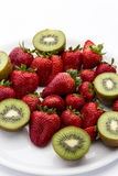 Strawberries and halved kiwifruits. Ripe strawberries, red to deep red, on a white plate; surrounded by halved kiwifruits, yellow green to green Royalty Free Stock Images
