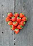 Strawberries in heart shape on wood background. Red strawberries in heart shape on wood background Royalty Free Stock Photography