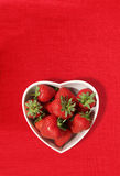 Strawberries in a heart shaped bowl Royalty Free Stock Images