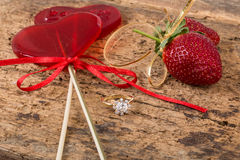 Strawberries, heart shaped candies and diamond ring Stock Photos