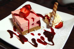Strawberries heesecake with cream. A delicious cheesecake with strawberries and cream royalty free stock photos