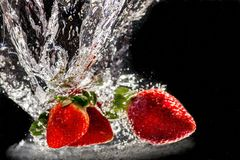 Strawberries i water. Three strawberries dropped into water Royalty Free Stock Images