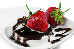 Strawberries on an ice cream drizzled by chocolate on a white p. Ripe red two strawberries on a white ice cream drizzled with chocolate sauce leaving a zigzag Stock Photo