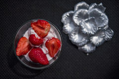 Strawberries and icecream. In transparent plate with silver petals royalty free stock images
