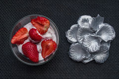 Strawberries and icecream. In transparent plate with silver petals. Brown Background. Texture royalty free stock images