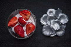 Strawberries and icecream. In transparent plate with silver petals. Brown Background. Texture royalty free stock photo