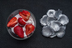 Strawberries and icecream. In transparent plate with silver petals. Brown Background. Texture stock photos