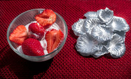 Strawberries and icecream. In transparent plate with silver petals. Red Background. Texture royalty free stock photo