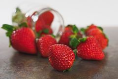 Strawberries in a jar and strawberries on a kitchen table royalty free stock photos