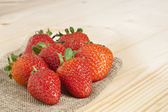 Strawberries on jute. Natural wood Stock Images