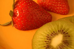 Strawberries and Kiwi. A colorful selection of sliced strawberries and kiwi presented on a gold plate stock photos