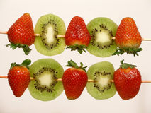 Strawberries and kiwi skewers. Two skewers of strawberries and kiwi ready to be eaten royalty free stock photography