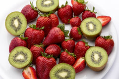 Strawberries and kiwis. A plate filled with ripe, deep red strawberries and halved kiwis Royalty Free Stock Photography