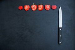 Strawberries and knife on black background Stock Images