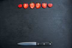 Strawberries and knife on black background Royalty Free Stock Photos