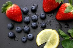 Strawberries, lemon slices, mint leaves and blueberries on black slate background. Three ripe strawberries with some mint leaves, Lemon slices and group of stock photo