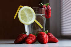 Strawberries lemon and water. When life gives you lemons, add strawberries and glass of water Royalty Free Stock Image