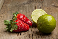 Strawberries and lime. Tow fresh strawberries and green lime on old wooden table Royalty Free Stock Images