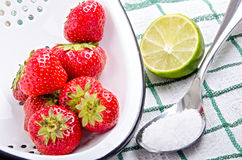 Strawberries with lime and sugar on a spoon Royalty Free Stock Images