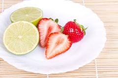 Strawberries and lime on white plate Stock Images