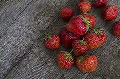 Strawberries lying on a crude wooden surface Royalty Free Stock Image