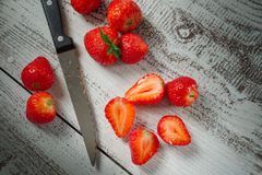 Strawberries lying on a wooden table with a knife. Close-up of whole and cut ripe strawberries lying on a wooden table with a knife Royalty Free Stock Photos