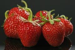 Strawberries macro. Fresh strawberries on black background stock image