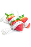 Strawberries and measure tape isolated on whi Stock Photography