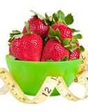 Strawberries and Measuring Tape. Green bowl of strawberries with a yellow measuring tape in front of it Royalty Free Stock Photos