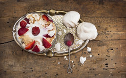 Strawberries and meringue in glass bowl on vintage tray Royalty Free Stock Images