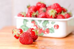 Strawberries in a metal bowl on the table, next to the three bal Stock Photo