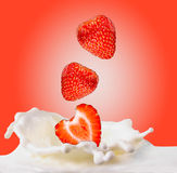 Strawberries & milk. Strawberries fall in milk on red background Stock Photo